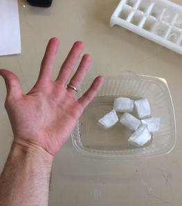 What happens to our hand temperature when we hold on to ice cubes?